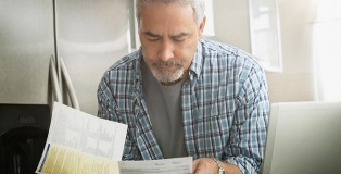older-man-looking-down-at-papers-bills-getty-mst